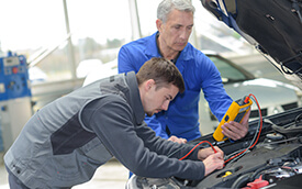 student with teacher reparing a vehicle