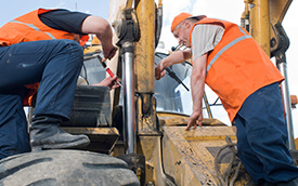 men doing maintenance on mobile machinery